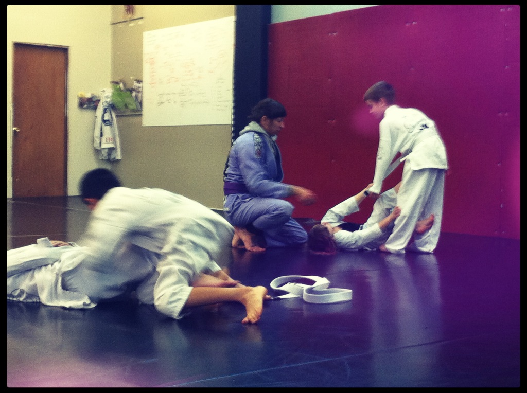 Kids martial arts class, getting pointers in individual drills from Coach Amanda