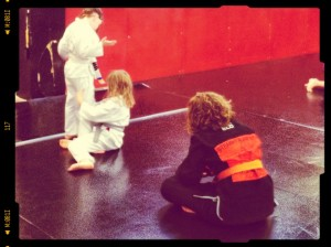 Teen coach watchin gover a drill in kid's martial arts class